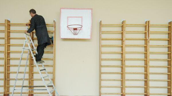 Учитель труда ремонтирует шведскую стенку в спортивном зале школы