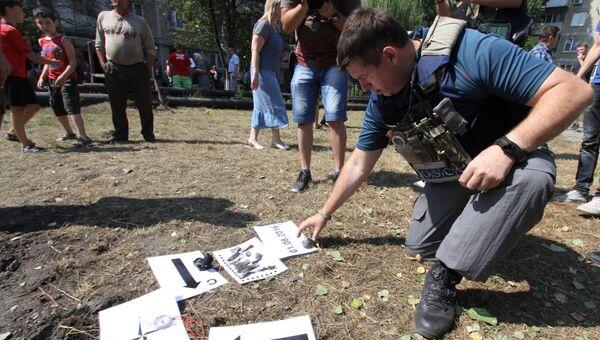 Представитель Специальной мониторинговой миссии ОБСЕ осматривают воронку от снаряда во время фиксации разрушений в Ясиноватой. Архивное фото