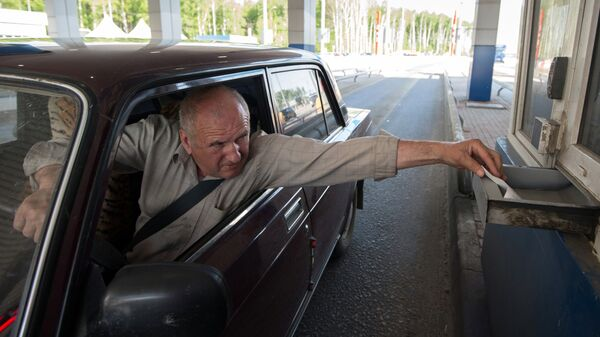 Водитель оплачивает проезд на контрольно-пропускном пункте на платном участке автомобильной дороги М-4 Дон в Московской области. 2013 год
