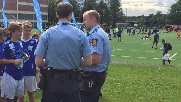 Полицейские разговаривают с игроками юниорской команды Херд на детском футбольном турнире Norway Cup