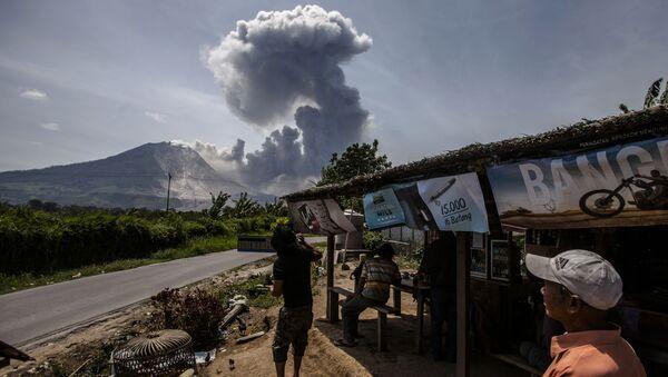 Индонезийские жители смотрят на извержение вулкана Синабунг