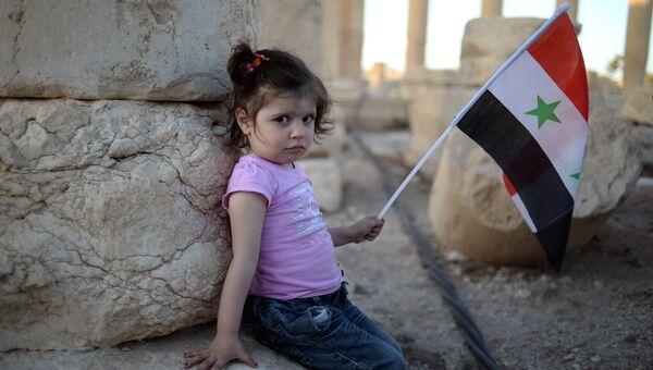 Девочка с сирийским флагом в исторической части Пальмиры