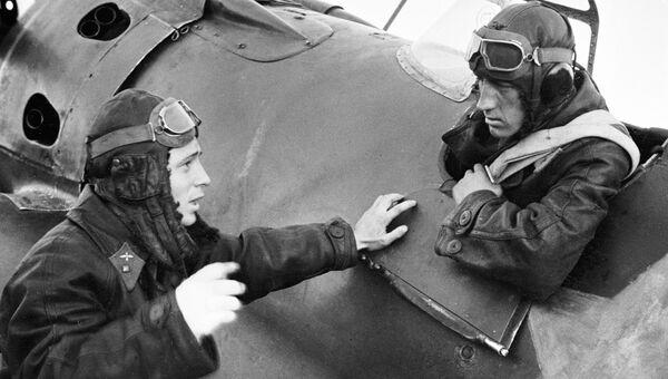 Летчик-истребитель, Герой Советского Союза, младший лейтенант Виктор Васильевич Талалихин беседует со своим боевым товарищем, сидящим в кабине самолета. Август 1941 года