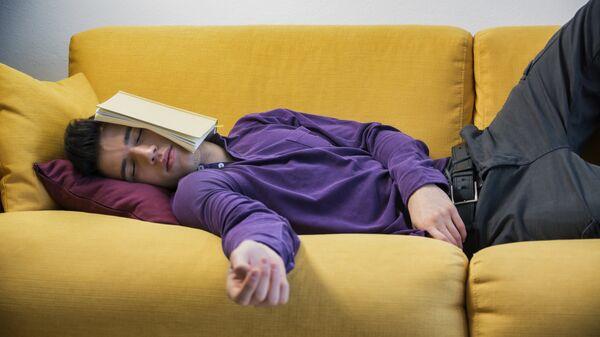 Мужчина отдыхает на диване с книгой. Архивное фото