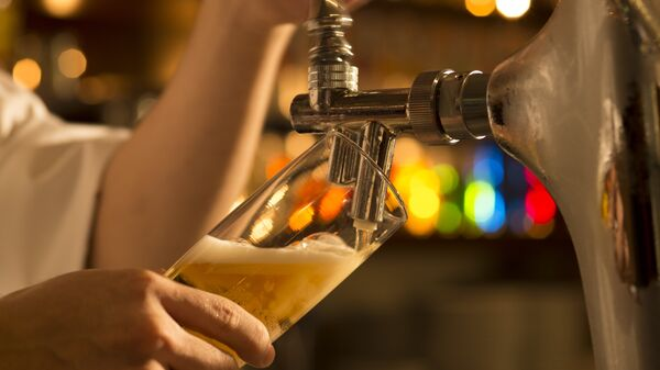 Бармен наливает пиво в бокал
