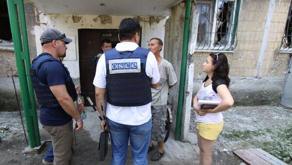 Представители ОБСЕ разговаривают с жителями дома в Ясиноватой в Донбассе, пострадавшего в результате обстрела города со стороны украинских силовиков. Август 2016