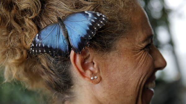 Бабочка сидит на ухе у посетительницы Аквариума Генуи