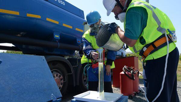 Сотрудники АЗС берут пробу бензина во время приемки бензовоза
