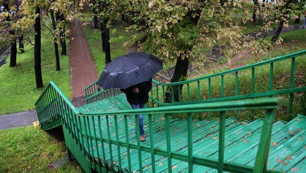 Прохожий во время дождя в Москве. 15 августа 2016