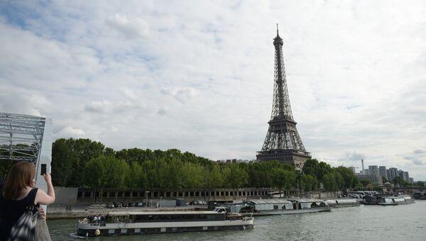 Девушка фотографирует с моста Эйфелеву башню в Париже. Архивное фото