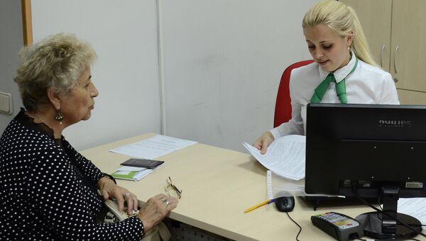 Женщина оплачивает коммунальные платежи в Российском национальном коммерческом банке в Крыму. Архивное фото