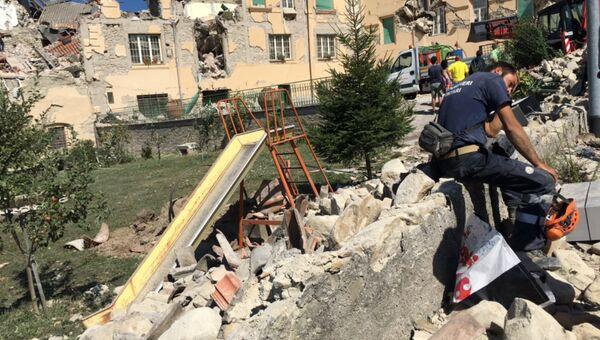 Люди у разрушенных в результате землетрясения домов в городе Аматриче