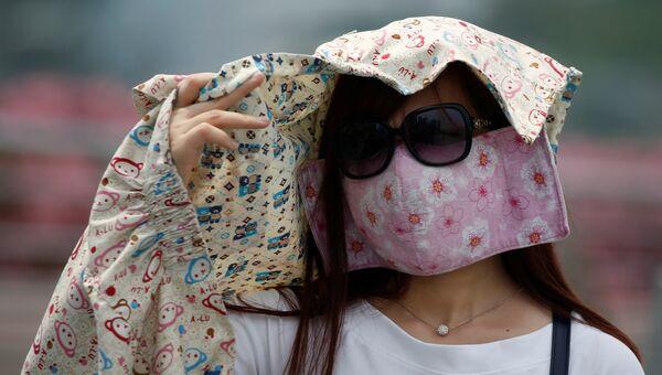 Женщина в защитной маске во время смога в Сингапуре. 26 августа 2016