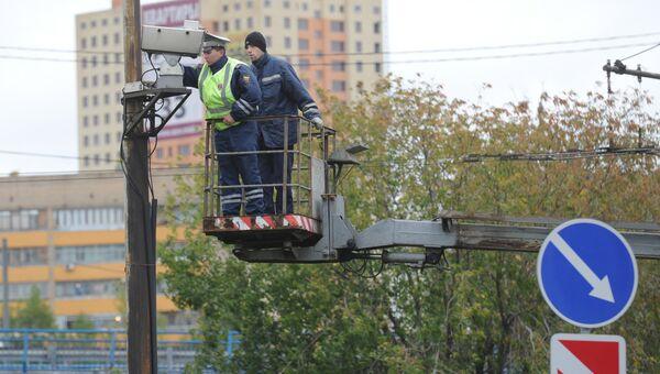 Сотрудник ДПС настраивает камеру автоматической фиксации нарушения правил дорожного движения в Москве. Архивное фото