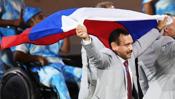 Директор Республиканского центра олимпийской подготовки по легкой атлетике, представитель белорусской делегации Андрей Фомочкин с флагом России на церемонии открытия XV летних Паралимпийских игр 2016 в Рио-де-Жанейро. 8 сентября 2016