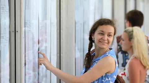 Девушка радуется своей фамилии в списках зачисленных абитуриентов