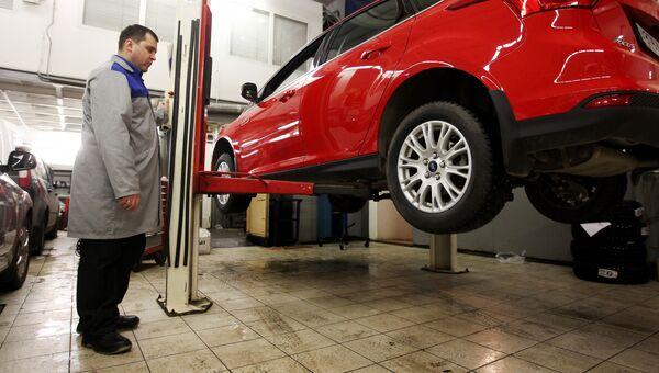 Сотрудник сервисного центра осуществляет технический осмотр транспортного средства