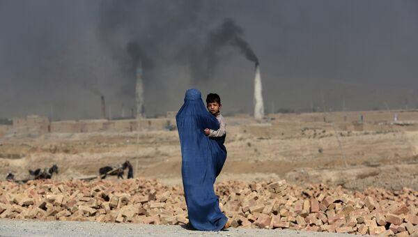 Женщина с ребенком на руках идет мимо кирпичного завода на окраине Кабула, Афганистан, архивное фото