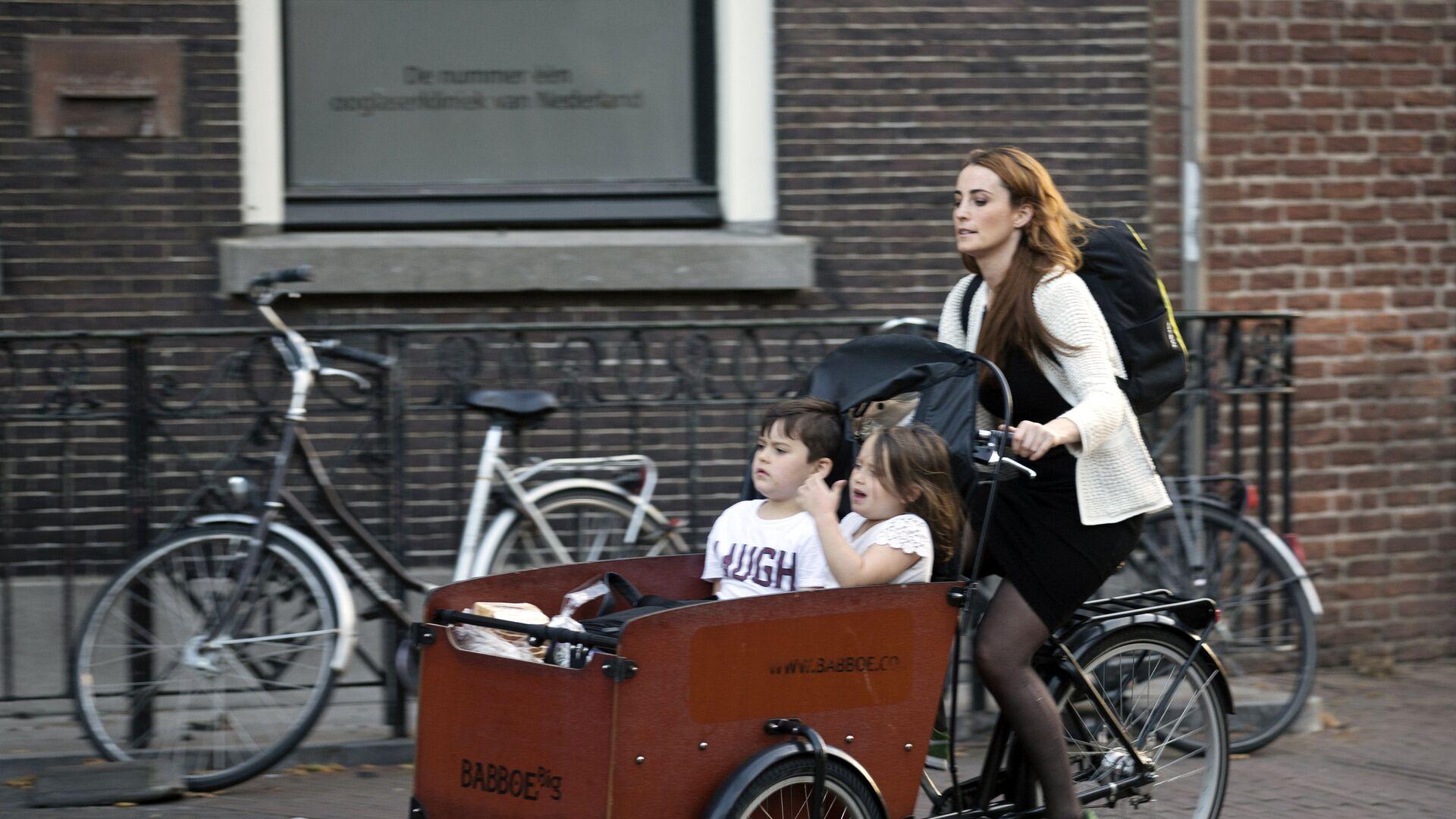 Женщина на велосипеде с детьми на одной из улиц Утрехта - РИА Новости, 1920, 03.09.2020