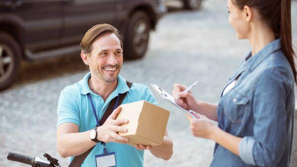 Курьер улыбается во время доставки посылки