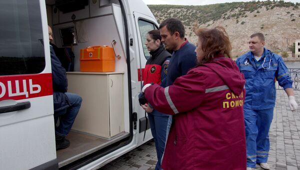 Сотрудники скорой помощи и один из спасенных членов экипажа плавучего крана, затонувшего у берегов Крыма, в порту Балаклавы