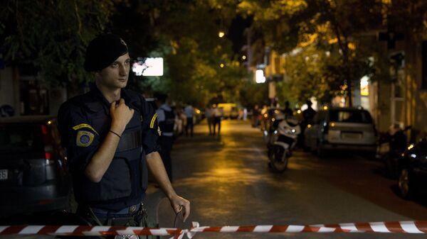 Сотрудник полиции возле места взрыва в Афинах, Греция. 12 октября 2016