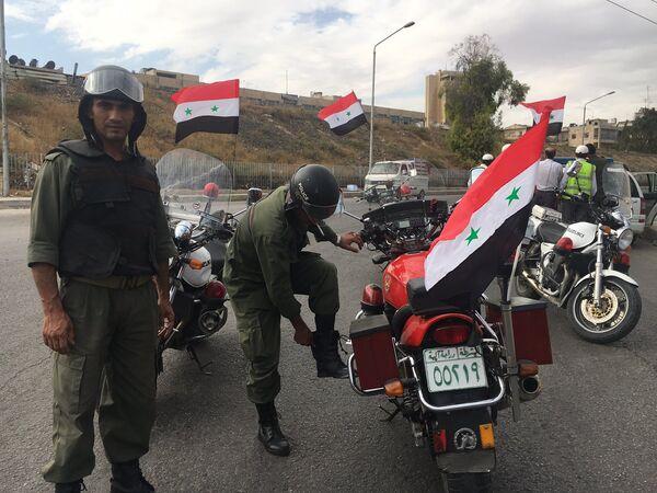 Сотрудники полиции готовятся к выходу мирных граждан и боевиков из восточного Алеппо.
