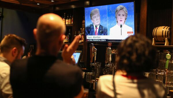 Люди смотрят трансляцию дебатов между Дональдом Трампом и Хиллари Клинтон. 19 октября 2016. Архивное фото