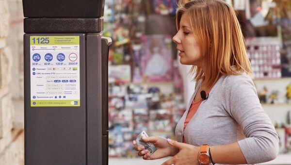 Женщина у парковочного автомата в пилотной зоне в историческом центре Санкт-Петербурга