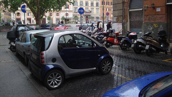 Припаркованные на улице Рима транспортные средства, Италия. Архивное фото