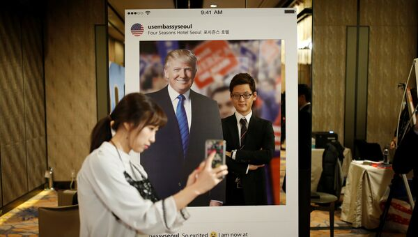 Девушка фотографирует своего друга на фоне портрета кандидата в президенты США Дональда Трампа в отеле в Сеуле