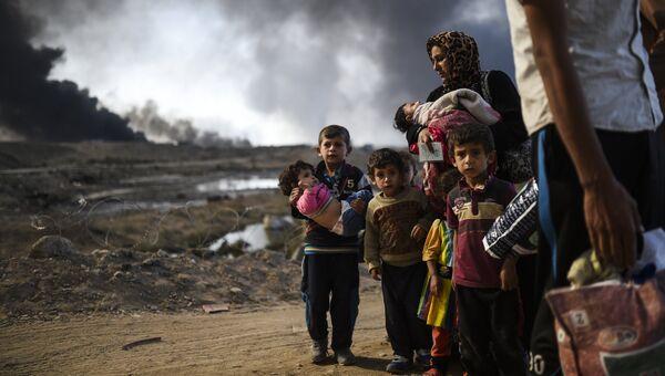 Иракская семья во время проведения операции против ИГ в Каяре в югу от Мосула. Архивное фото