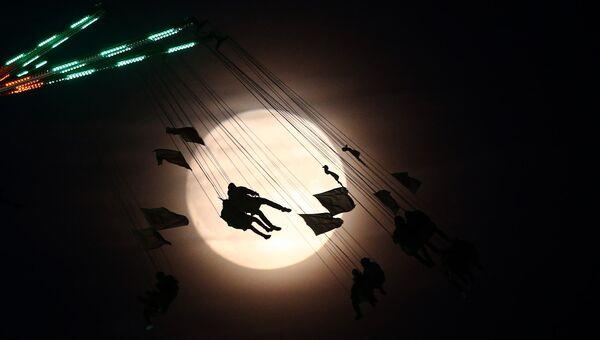 Люди катаются на каруселях на фоне луны в Лондоне, Великобритания. 13 ноября 2016
