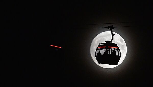 Канатная дорога на фоне луны в Лондоне, Великобритания. 13 ноября 2016