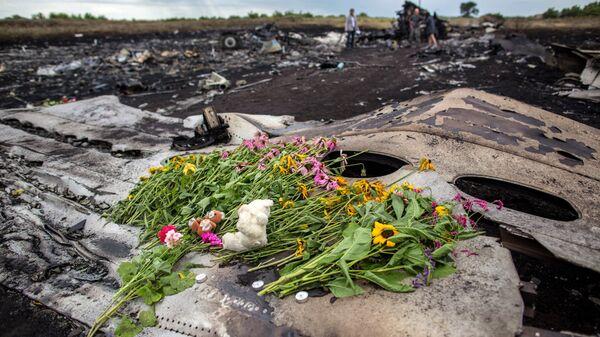 Цветы на фюзеляже лайнера Boeing 777 Малайзийских авиалиний, потерпевшего крушение в районе города Шахтерска Донецкой области
