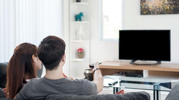 Молодая пара смотрит телевизор