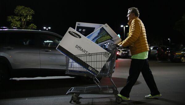 Покупатель выходит из магазина во время распродажи в Черную пятницу в Сан-Диего, штат Калифорния, США