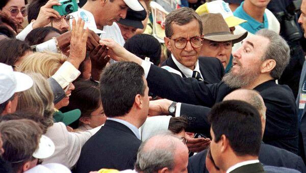 Президент Кубы Фидель Кастро приветствует людей, пришедших на мессу с Папой Иоанном Павлом II на площади Революции в Гаване. 25 января 1998