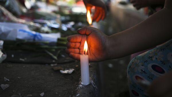 Жители Сантьяго зажигают свечи в память о Фиделе Кастро перед посольством Кубы, Чили