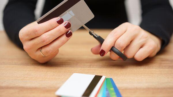 Девушка разрезает пластиковую карту