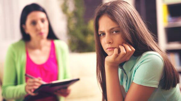 Профессиональный психолог работает с девочкой-подростком. Архивное фото