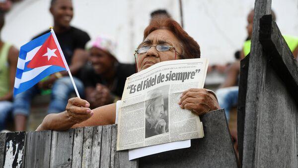 Женщина ожидает траурный кортеж с прахом команданте Фиделя Кастро в Сантьяго-де-Куба