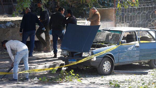 Сотрудники органов безопасности и следователи на месте взрыва бомбы на улице эль-Харам в Каире, Египет