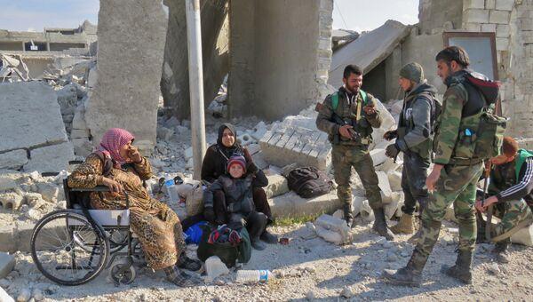 Солдаты правительственных войск и местные жители в одном из освобожденных от боевиков районов Алеппо, Сирия. 12 декабря 2016