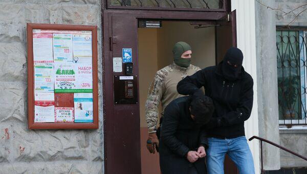 Силовики выводят из подъезда дома № 11 на улице Наметкина одного из участников диверсионно-террористической группы, готовившей серию терактов в Москве