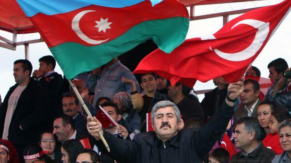 Мужчина с флагами Азербайджана и Турции