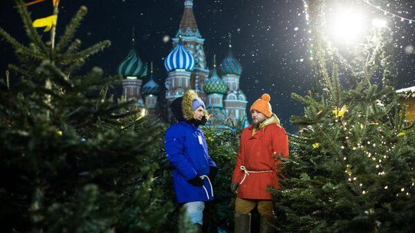 Продавцы на елочном базаре ГУМ-Ярмарки на Красной площади в Москве