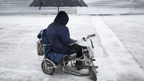 Мужчина в инвалидной коляске, под зонтом, на одной из улиц Симферополя