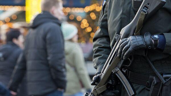 Сотрудник правоохранительных органов Германии патрулирует рождественскую ярмарку
