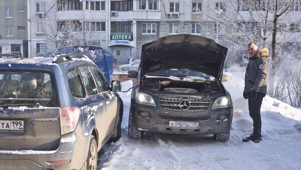 Автомобилист заряжает аккумулятор своего автомобиля в Москве